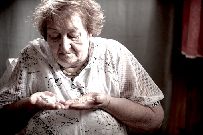 Sad old woman holding drugs.