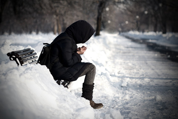 Winter time—person sitting on a bench in a snowy park