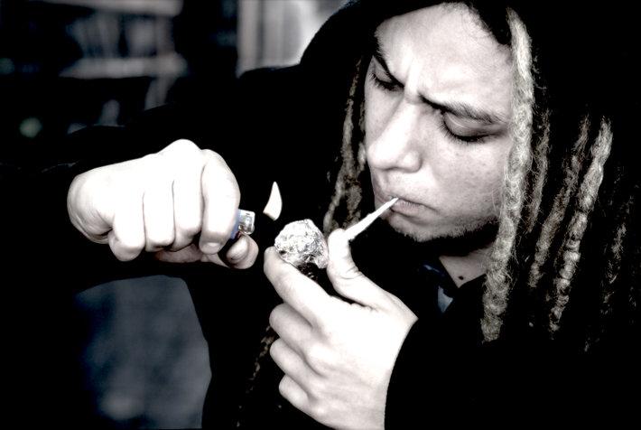 Guy with dreadlocks smoking marijuana