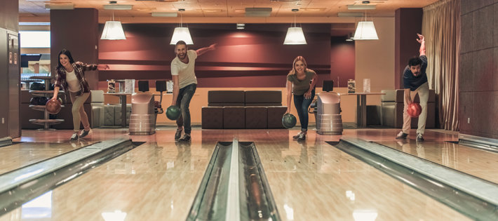Friends are having fun by playing bowling