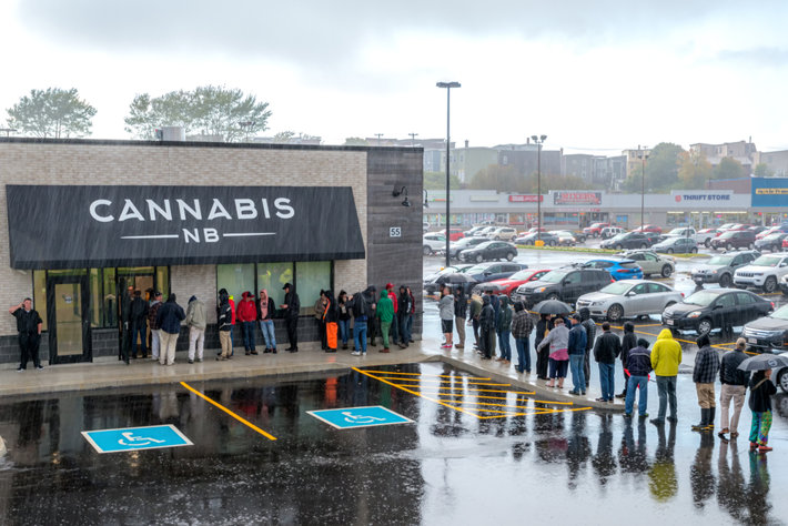 People standing in a line under the rain for cannabis.