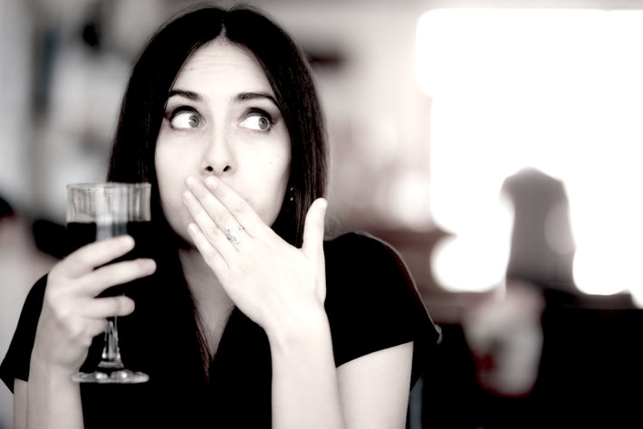 Surprised woman drinking alcohol