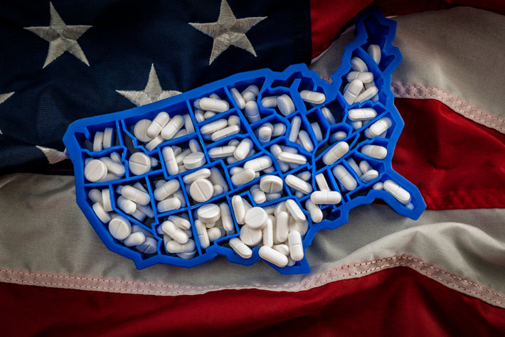 America shaped pills container on USA flag.