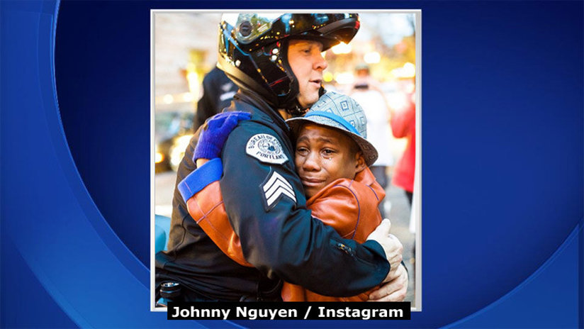 Black boy hugging white officer