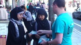 ロンドンの大通りを歩く若者や大人に薬物乱用防止教育の小冊子が配布されています。