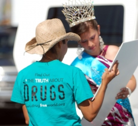A youth volunteer assists Miss Guatemala, a special guest of the festivities, as she signs a drug-free pledge.