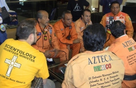 Within 24 hours of the disaster a team of Los Topos Mexican search and rescue specialists gathered in Mexico City to work out logistics for their travel to Japan (funded by the Volunteer Ministers). Many of the Los Topos personnel have trained as Volunteer Ministers themselves, and all of them wear the Volunteer Minister symbol on their bright orange uniforms.