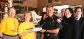 Pasadena Scientology Volunteer Ministers and graduates of the Pasadena Emergency Response Training program present a check.