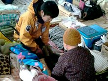 A Scientology Volunteer Minister caring for an elderly woman in Kesennuma.