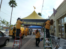 Volunteer Ministers from the Church of Scientology of Tampa, Florida, set up their bright yellow tent as part of the 65th annual Fiesta Day Celebration in Ybor City, Florida.
