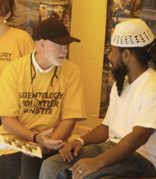 A Scientology Volunteer Minister helps a visitor address a personal problem at the Volunteer Ministers tent at the Manatee County Fair.