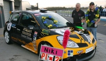 Niki Lanik avec ses médailles et sa voiture de course portant le logo de l'association Des jeunes pour les droits de l'Homme