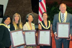 Zástuce státu Hawaii Rida Cabanilla (vlevo) zastupující sněmovnu representantů s ocenením pro Mezinárodní Scientologickou církev a tři scientology z Hawaie v březnu 2013 za jejich příspení za zlepšení společnosti
